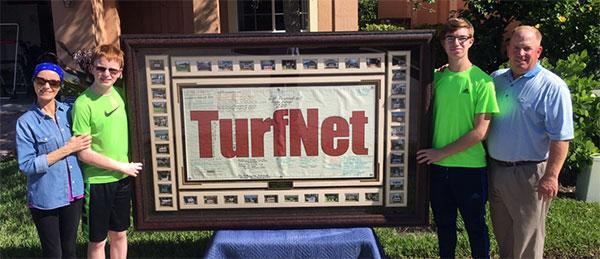Peggy, Robert, Kevin and John Colo with a framed TurfNet banner, November 2017.