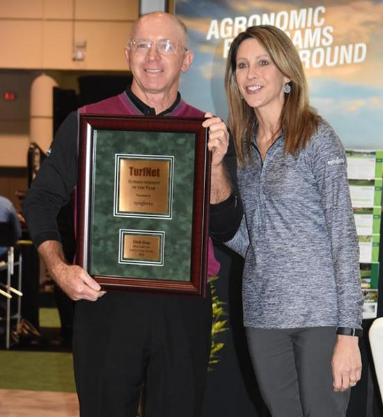 Stephanie Schwenke of Syngenta presents Dick Gray of PGA Golf Club in Port St. Lucie, Florida, with the TurfNet Superintendent of the Year Award.