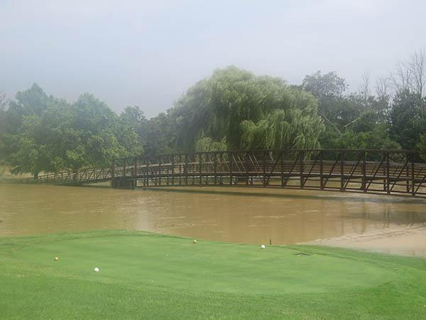 Both ends of bridge spanning the Blanchard River on No. 18 at Findlay Country Club were under water after recent rains swamped four holes on the course.