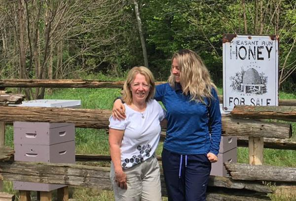 Pheasant Run Golf Club superintendent Leasha Schwab, right, with her mother, Laurie Simard, at the club's beekeeping operation.