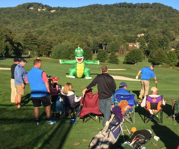 Highlands Cup participants take aim at an inflatable dinosaur as part of the event's skills competition.